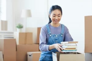 young woman packing up belongings to use student self storage