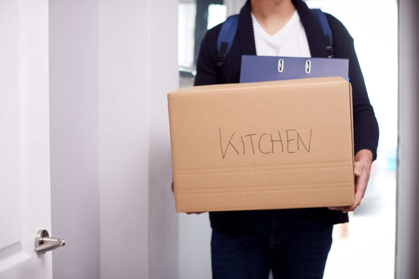 student moving into university with self storage cardboard box
