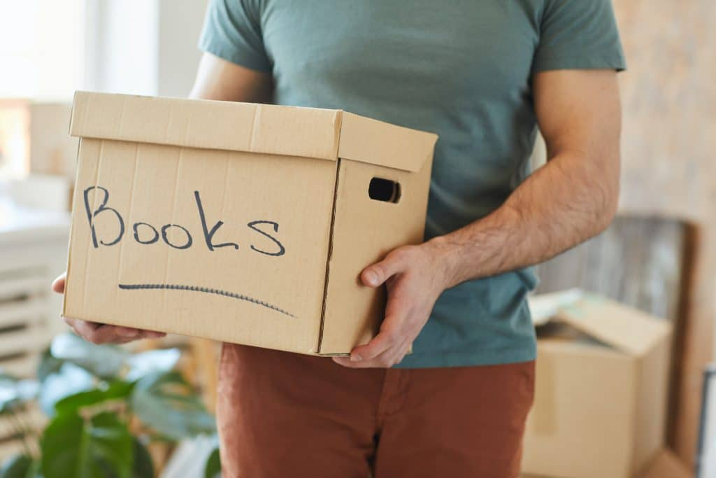 man carrying box of books for storage