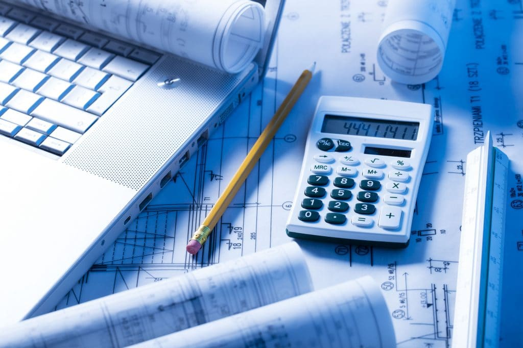 blueprints, calculator and laptop, construction and finance theme
