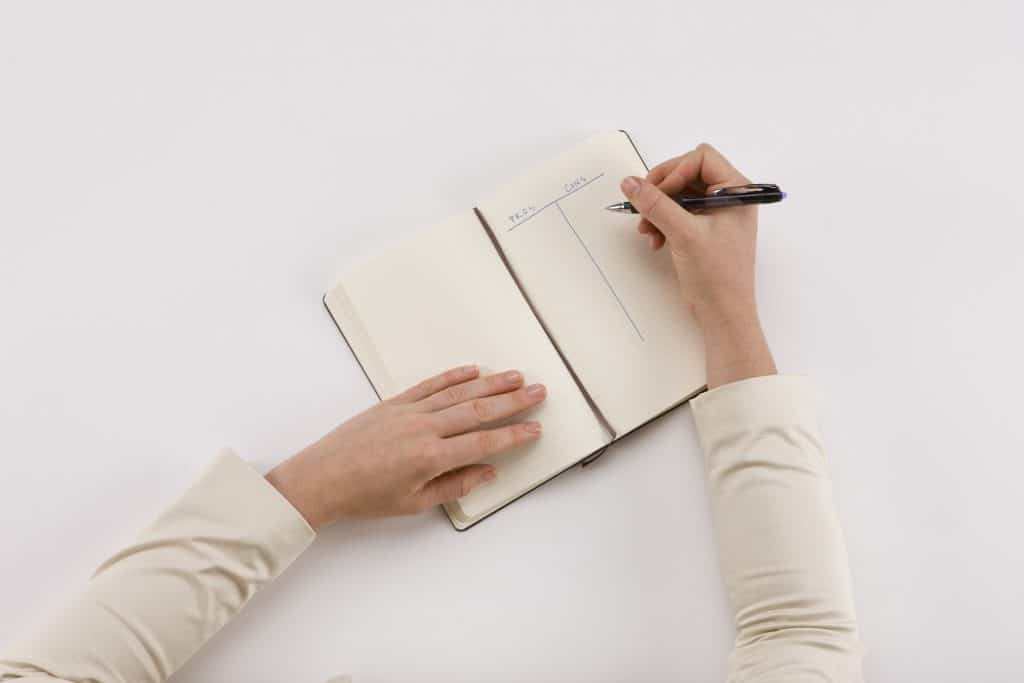 woman writing pros and cons list