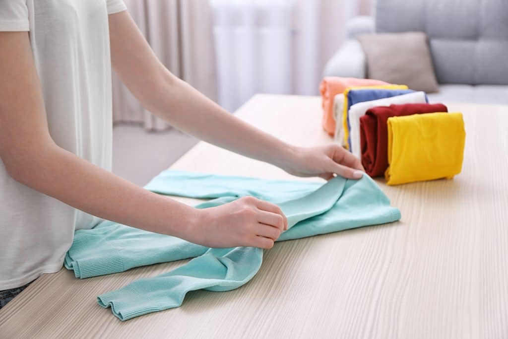 Woman folding jumper for clothing storage
