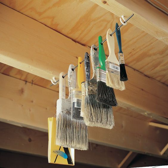 paintbrushes hanging from ceiling storage in shed